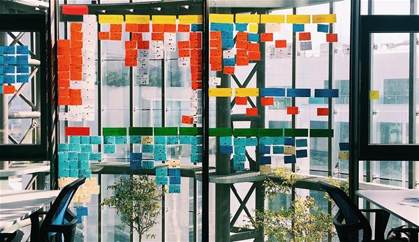 Conference room with dozens of sticky notes on the windows.